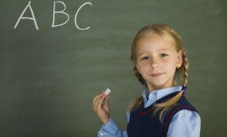 黒板にアルファベットを書く外国の少女