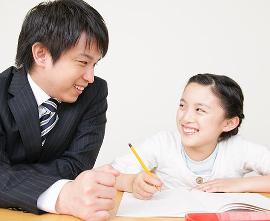 先生と笑顔で向き合う小学生